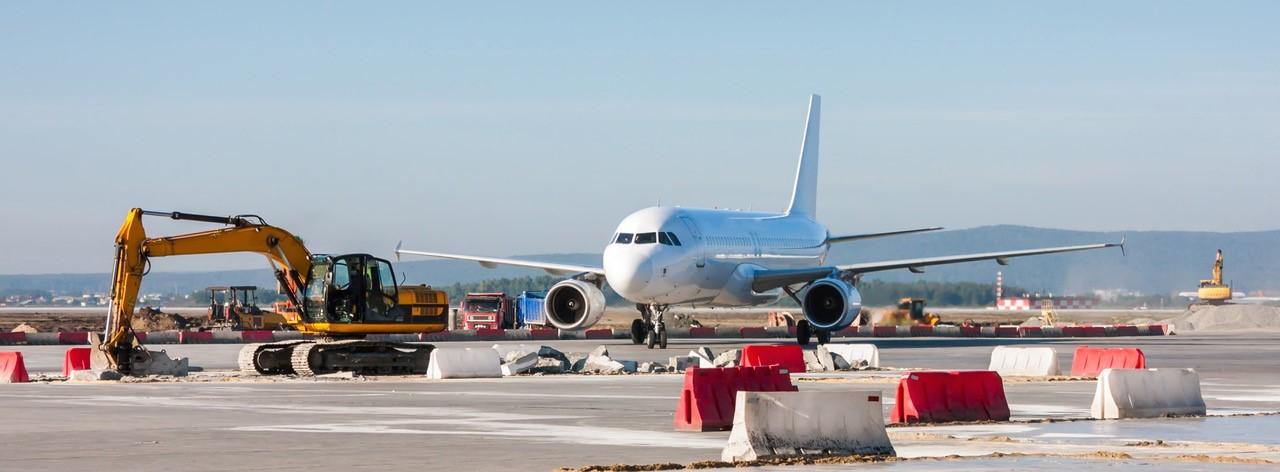 Flughafenausbau: Flugzeug auf Rollfeld mit Bagger