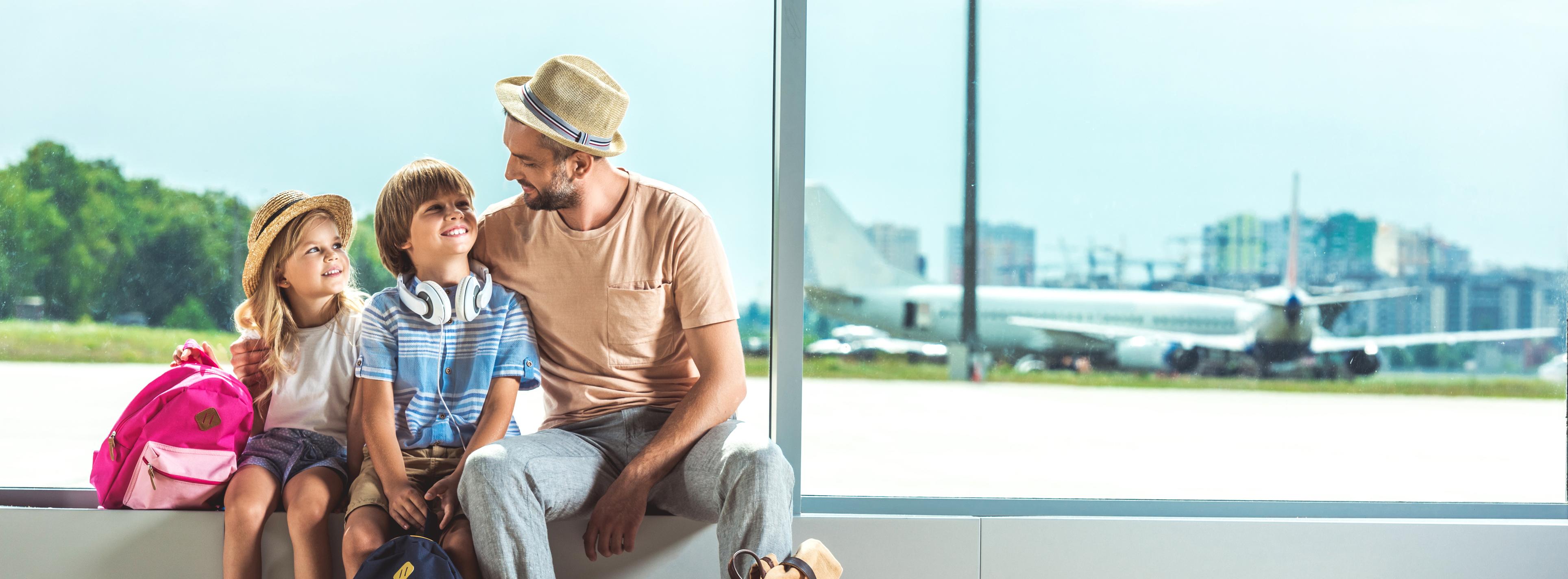 Vater wartet mit Kindern auf Flug